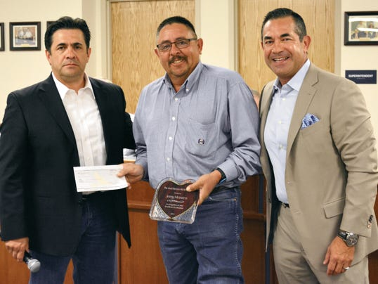 Elena Ruiz - Headlight Photo   Brothers Jimmy Herrera, left, and Michael Herrera, right, presented Red Mountain Middle School shop teacher Jerry Montes with the Fred Herrera Heart Award. The award also came with a 1,500 check.
