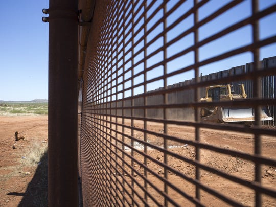 Finishing work is done in May 2017 on bollard-style fencing in Naco, Arizona.