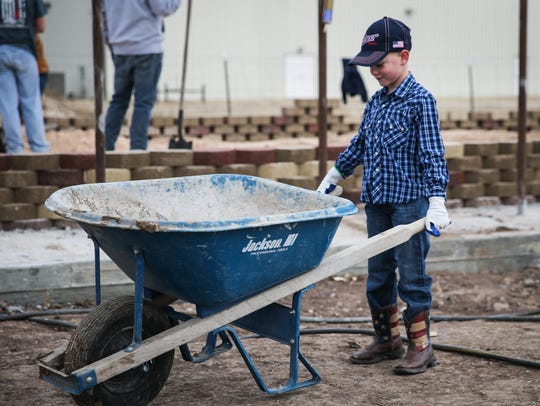Gunner Townley, 7, pushes a wheel barrow while volunteers