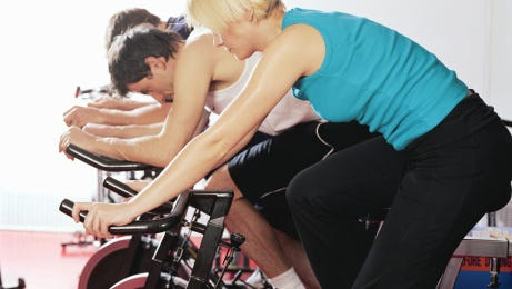 Three people on exercise bikes, side view
