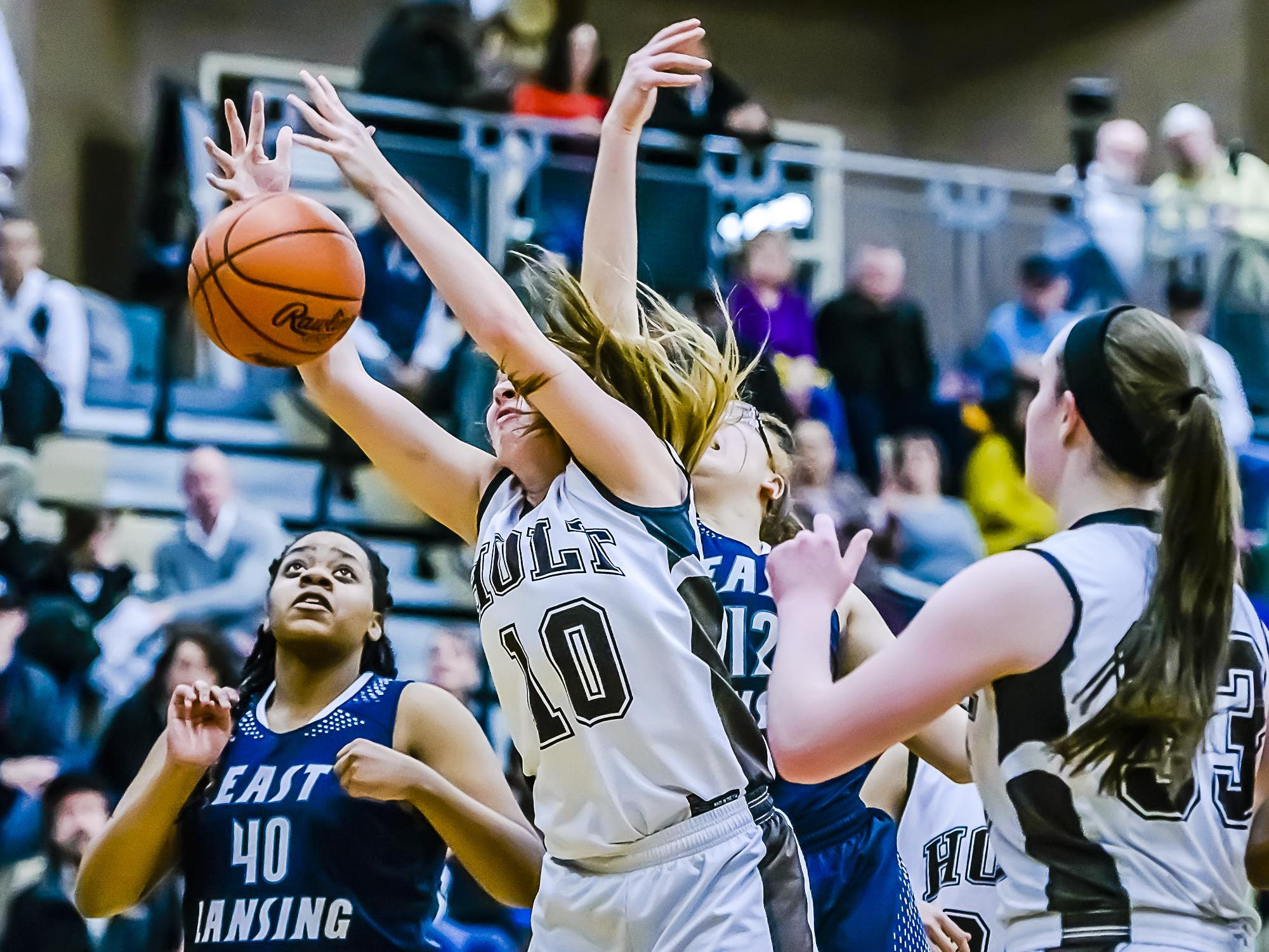 Rylee Stiles ,10, of Holt reachses for a rebound as Zion Keyes ,40, of East Lansing looks on during their game Friday January 15, 2016 in Holt. KEVIN W. FOWLER PHOTO