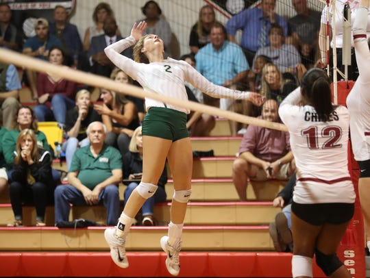 Lincoln's Amber Grant leaps to spike the ball against
