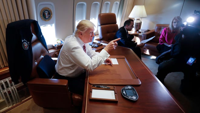 President Trump points to members of the media while sitting at his desk on Air Force One upon his arrival at Andrews Air Force Base, Md. on Jan. 26, 2017.
