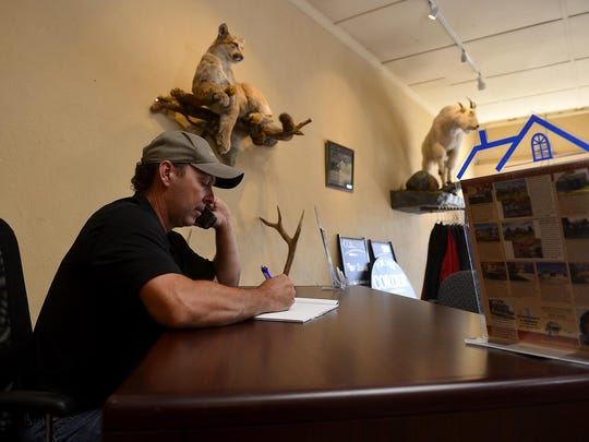 Trampus Corder of Corder and Associates real estate business in Fort Benton works at his desk.