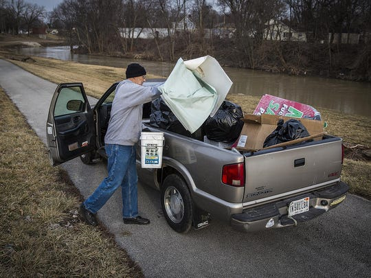 Ed Zeigler volunteers his time picking up trash along the White River Friday afternoon. Zeigler said his truck fills up with trash quickly, especially after high water leaves some of the trash from the river on shore.