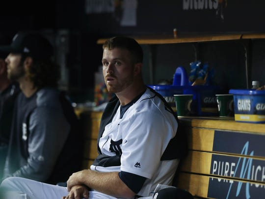 Tigers' Buck Farmer sits in the dugout during the sixth