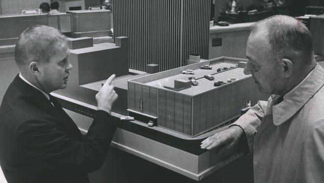 Marshall & Ilsley Bank President Jack A. Puelicher explains features of the bank and parking building the bank proposes to build downtown to customer George Banzhaf of Fox Point in this photo, taken Oct. 9, 1964. This photo was published in the Oct. 9, 1964, Milwaukee Journal.
