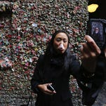 Silvia Lim's gum bubble bursts as she records with her phone. Visiting from Sweden, she takes a self-portrait at the the Gum Wall attraction in Seattle's Post Alley.