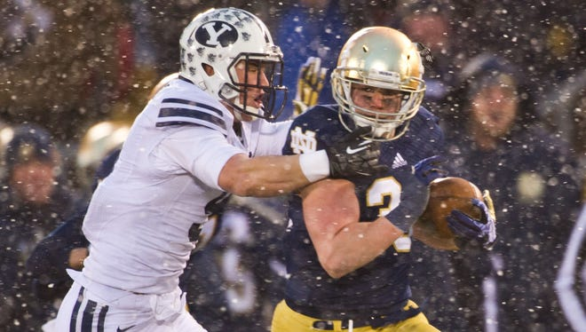 Notre Dame running back Cam McDaniel (33) carries the ball as BYU linebacker Alani Fua (5) defends in the second quarter Saturday at Notre Dame Stadium.