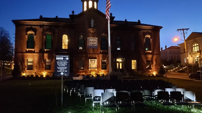 The Empty Chair Memorial at night in front of Town Hall.