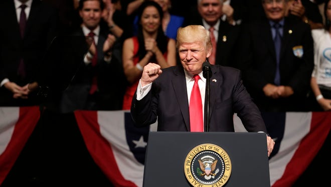 President Trump clenches his fist as he announces a revised Cuba policy in Miami.