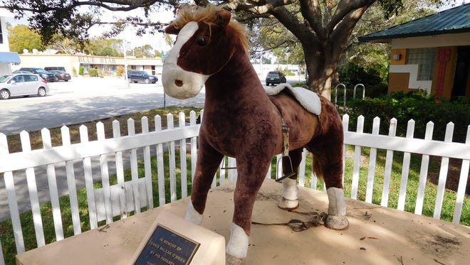 A stuffed toy horse dubbed Mini Patriot apparently is holding the place of Patriot, a fiberglass statue out for repairs that normally occupies the spot in Vero Beach.