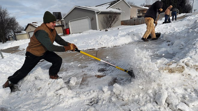 Djani Dautcehajik with All Seasons Property Maintenance works to loosen snow crusted on the sidewalk off of 26th Street in western Sioux Falls on Wednesday, Jan. 14, 2015.