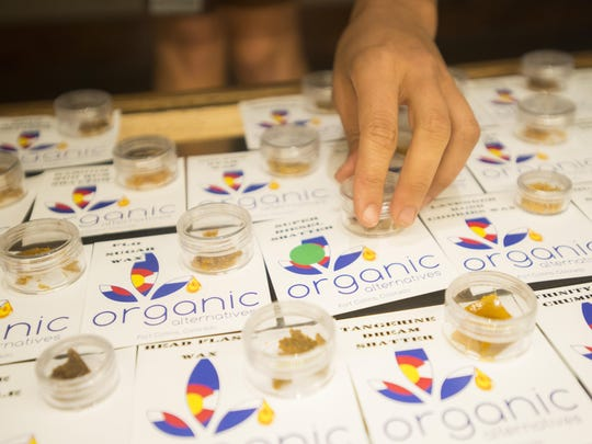 An employee at Organic Alternatives marijuana dispensary in Fort Collins removes concentrated marijuana from a display case in this file photo.