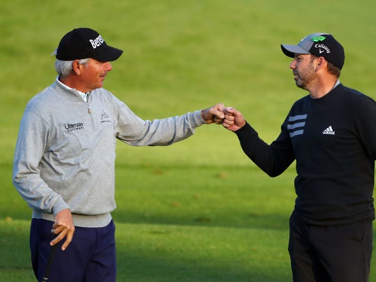 Masters champions Fred Couples and Sergio Garcia fist-bump on the driving range for the Masters golf tournament at Augusta National GC.