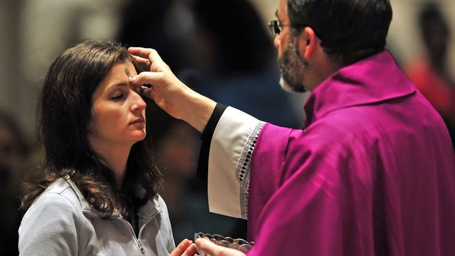 A person receives ashes from Father John Sims Baker during a previous Ash Wednesday service at Cathedral of the Incarnation in Nashville. Some churches in Middle Tennessee are canceling or rescheduling Ash Wednesday services due to icy roads.
