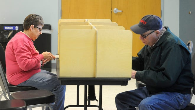 Gayle Lunski and Ralph Gould vote in a school board election that includes a school calendar measure at Kenny Anderson Community Center in Sioux Falls, S.D., Tuesday, April 14, 2015.