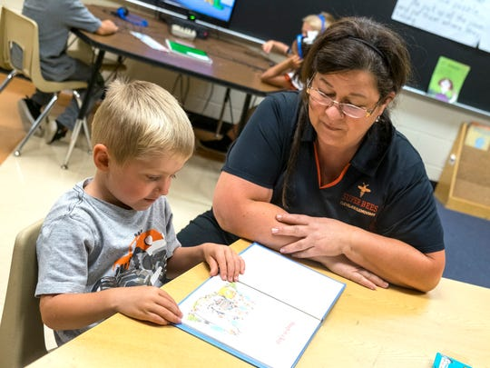 Cleveland Elementary paraprofessional Antoinette Vultaggio reads with a kindergartener and talks about rhyming words Aug. 29. Starting in the 2018-2019 school year, Cleveland Elementary School will house kindergarten through second grade and will focus on literacy.