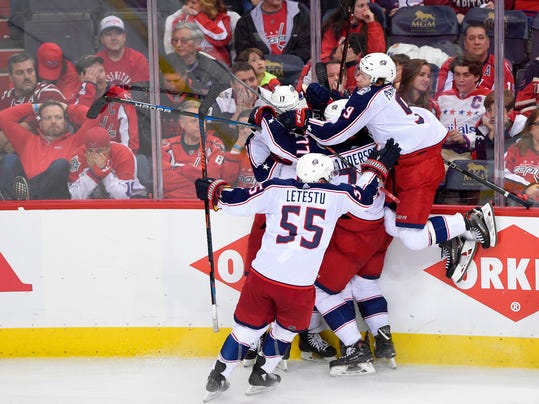 Columbus Blue Jackets left wing Matt Calvert, obscured, celebrates his game-winning goal with Artemi Panarin (9), Mark Letestu (55), Josh Anderson (77), Brandon Dubinsky (17) during overtime in Game 2 of an NHL first-round hockey playoff series against the Washington Capitals, Sunday, April 15, 2018, in Washington. The Blue Jackets won 5-4 in overtime. (AP Photo/Nick Wass)