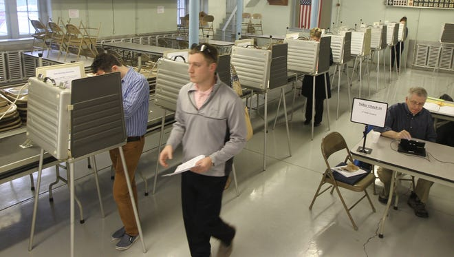 Cory Bastian carries his ballot to a scanner after voting at St. Rose Church in the East End.