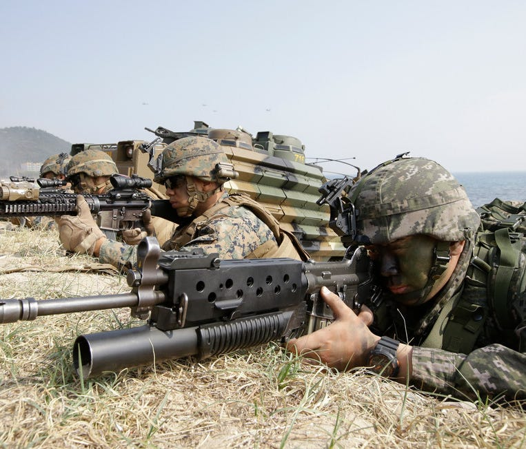 In this March 30, 2015, file photo, a South Korean Marine, right, and U.S. Marines aim their weapons during joint military exercises.