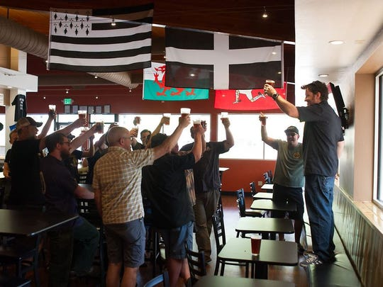 Fort Collins brewers toast a new collaboration beer at McCllelan's Brewing on Monday as part of American Craft Beer Week.