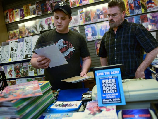 John Mizzer, right, manager/owner Comic World, and Andrew Melius are getting ready  Wednesday, May 4, 2016 for Free Comic Book Day at the Chambersburg Mall store.