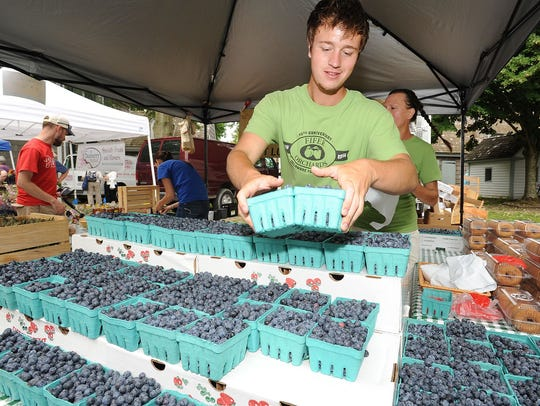 In this file photo, Kyle Brennan from Fifer Orchards puts fresh blueberries out for sale at the Lewes Farmers Market in 2014 when the event was held at the Lewes Historical Society Complex.