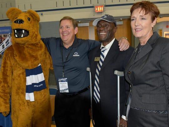 Lion mascot, left, Doug Harmon and Debra Collins get
