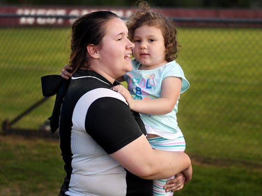 West Carroll High School's Ashley Barlow holds her 3-year-old daughter, Madalyn, in her arms after a game against Peabody, Monday, April 3. Barlow, a two-time cancer survivor and will graduate from high school, this month.