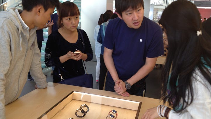 An Apple employee, second from right,  introduces the Apple Watch to customers in Beijing on Friday, the day of the new product's global launch.
