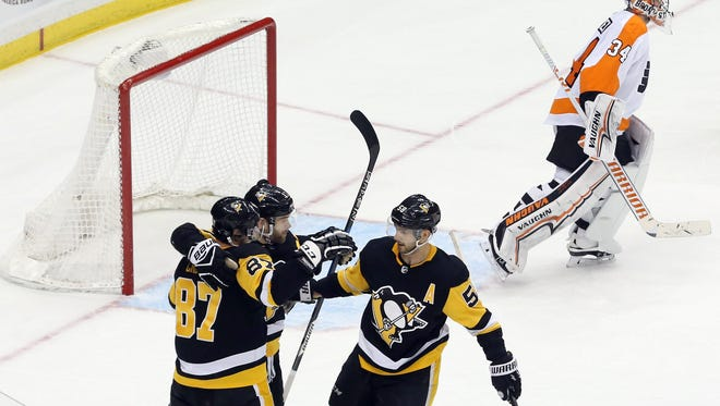 Flyers goaltender Petr Mrazek (34) reacts as the Pittsburgh Penguins celebrate a goal by right wing Bryan Rust (middle) in overtime.