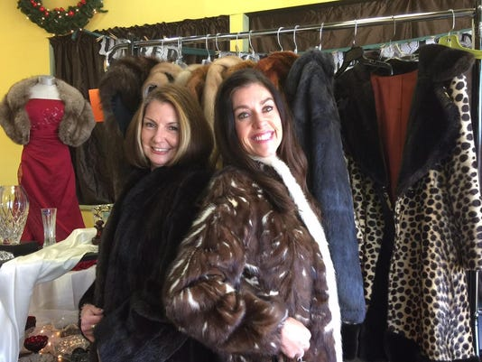 Jan Flood, left, and Anna Hogue model fur coats that have been donated to be