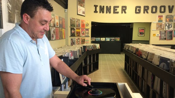 """Dave Frankel cleans a copy of the Beatles' """"Help!"""" album in his West Park Avenue record store Inner Groove Records in Merchantville."""