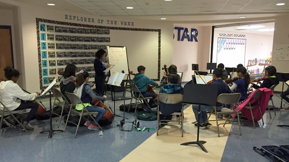 Orchestra students rehearse in a hallway at R.E.L.