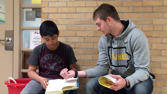 Iowa wide receiver Matt VandeBerg reads with sixth-grader Jhair Herrera at Twain Elementary School on Tuesday as part of the Hawkeye Readers program.