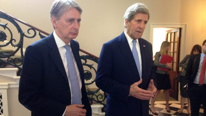 U.S. Secretary of State John Kerry, right, and British Foreign Secretary Philip Hammond speak to reporters at Carlton Gardens in London, May 12, 2016, after meeting with key European bankers. Kerry is working to reassure European banks they wont be penalized for conducting legitimate business with Iran.