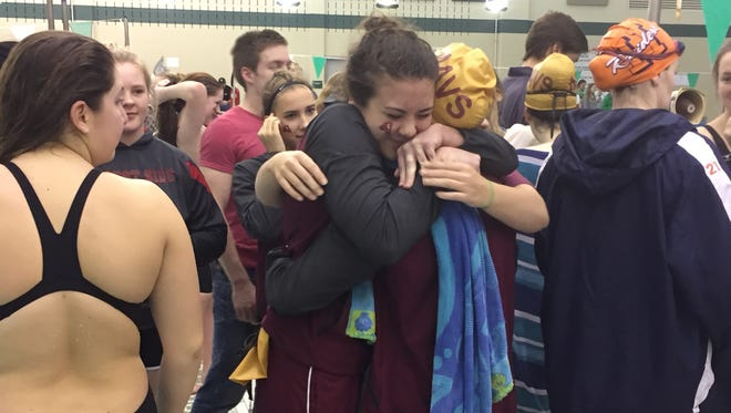 McCutcheon junior Emma Saunders congratulates teammate Kate Gallagher after Gallagher won the 500-yard freestyle at Saturday's Zionsville Sectional.