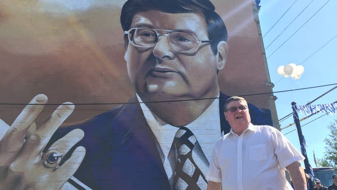 Former Kentucky basketball coach Joe B. Hall stands in front of a mural depicting him during a ceremony in Cynthiana, Kentucky on Tuesday July 25, 2017.