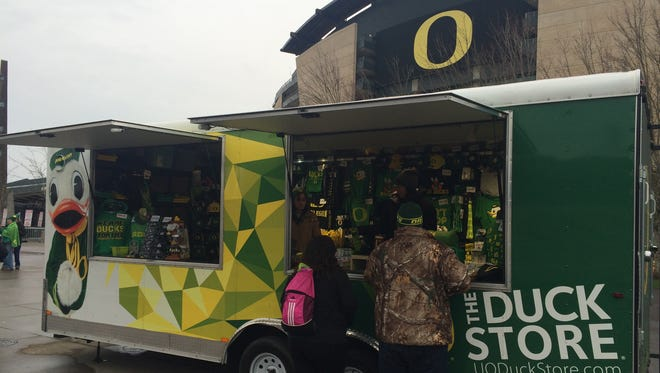 Fans buy some gear at the mobile Duck Store at Autzen Stadium on Saturday before the annual Civil War.