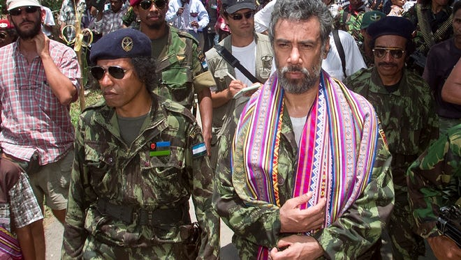 In this Oct. 24, 1999, photo, then-East Timorese rebel leader Xanana Gusmao, right, walks with Taur Matan Ruak, left, then commander of the Armed Forces of National Liberation of East Timor (FALINTIL) as he returns to the rebel army camp for the first time since his imprisonment by Indonesia, in Remexio, in the hills outside of Dili, East Timor. Gusmao resigned as prime minister on Friday, Feb. 6, 2015.