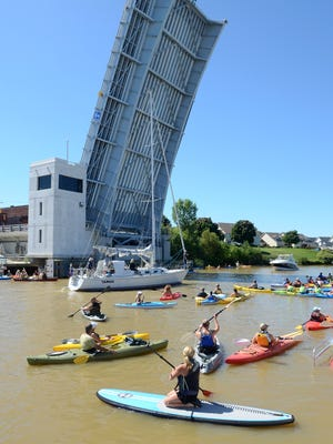 A sailboat passes under the 7th Street Bridge Sunday during the annual Paddle and Pour event in Port Huron.  ANDREW JOWETT/TIMES HERALD.