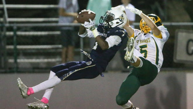 Delaware Military Academy's Corahn Alleyne makes a grab while defended by the Spartan's Ian Noonan at Baynard Stadium Friday.