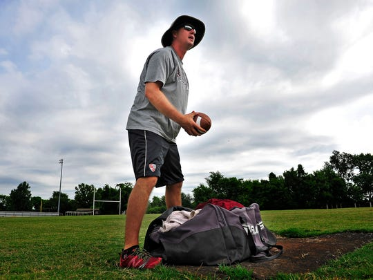 Former NFL quarterback Kelly Holcomb gets ready to coach players during practice at Riverdale High School in Murfreesboro, Tenn., Wednesday, July 29, 2015.