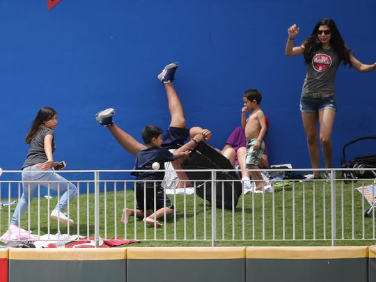 Fans scramble as a homerun ball landed in the left field grassy area Sunday.