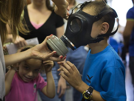 A woman shows her children how to put on a gas mask at a distribution center on Aug. 26 in Tel Aviv. Israel is distributing gas masks to civilians as tension rises over possible international military intervention In Syria.