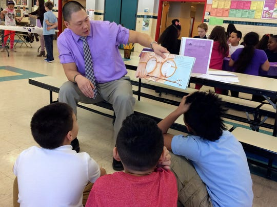 In this Feb. 14, 2017 photo, teacher Craig Muzzy reads a story about peer pressure to students at the Chamberlain Elementary School in New Britain, Conn., as part of the Love Wins program's Friendship Day. The emotional-learning program is designed to deal with the problem of social isolation and teach students about empathy. (AP Photo/Pat Eaton-Robb)