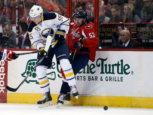 Buffalo Sabres defenseman Rasmus Ristolainen (55), from Finland, can't keep control of the puck with Washington Capitals defenseman Mike Green (52) behind him, in the first period of an NHL hockey game, Saturday, Nov. 22, 2014, in Washington. (AP Photo/Alex Brandon)