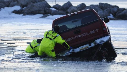Clay Township firefighters work on a vehicle that crashed through the ice on Lake St. Clair.
