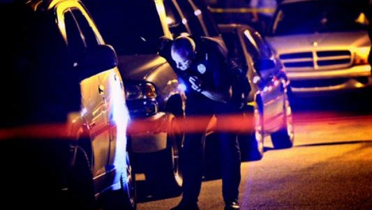 York City police officers search for evidence after Jordan Breeland, 21, was shot and killed Oct. 15, 2013.